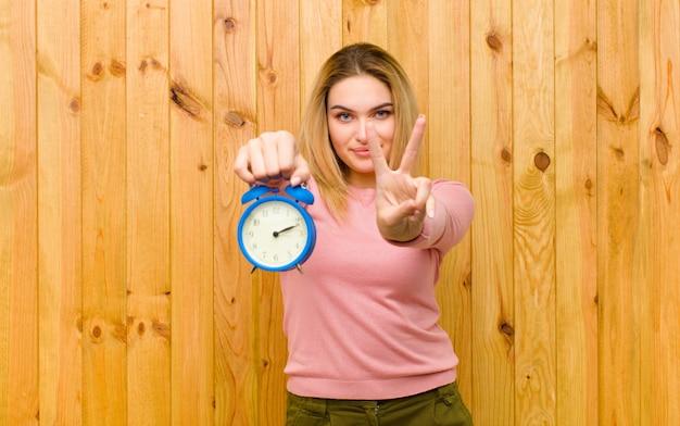 木製の壁に目覚まし時計で若いかなりブロンドの女性