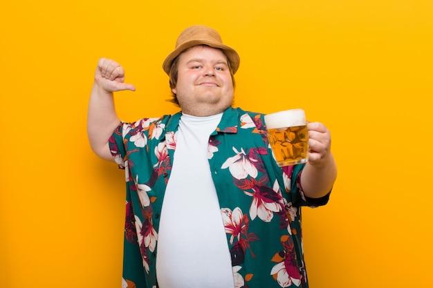 平らな壁にビールのパイントを持つ若い大きなサイズの男