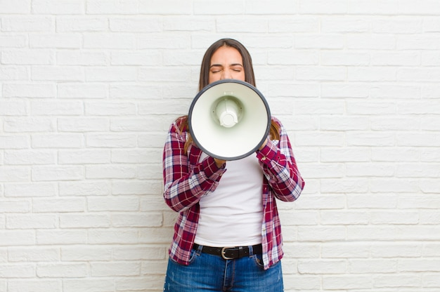 Молодая милая женщина с мегафоном против текстуры кирпичной стены