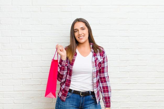 Молодая милая женщина с хозяйственными сумками против текстуры кирпичной стены
