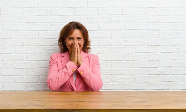 Женщина среднего возраста выглядит счастливой, веселой, счастливой и удивленной, закрывая рот обеими руками