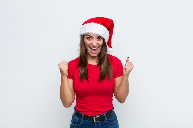 サンタの帽子を持つ若いきれいな女性。クリスマスのコンセプト。