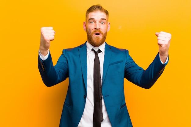 勝利者のような信じられないほどの成功を祝っている若い赤い頭の実業家、興奮して幸せそうに言ってそれを取る!