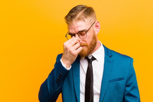 Молодой рыжий бизнесмен, чувствующий себя подчеркнутым, несчастным и расстроенным, касаясь лба и страдая мигренью сильной головной боли