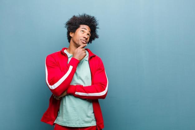 Молодой черный спортивный человек думает, чувствует себя сомнительным и смущенным, с различными вариантами, задаваясь вопросом, какое решение принять против гранж стены