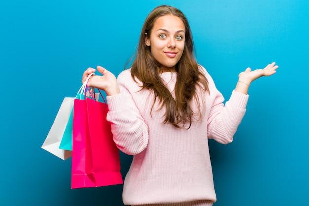 青い背景の買い物袋を持つ若い女
