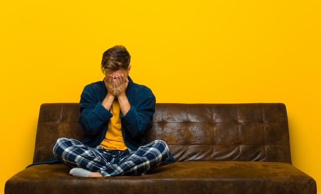 Молодой человек в пижаме чувствует себя грустным, разочарованным, нервным и подавленным, закрывает лицо обеими руками, плачет. сидя на диване