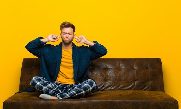 怒って、ストレスを感じ、イライラしているパジャマを着た若い男。ソファに座って