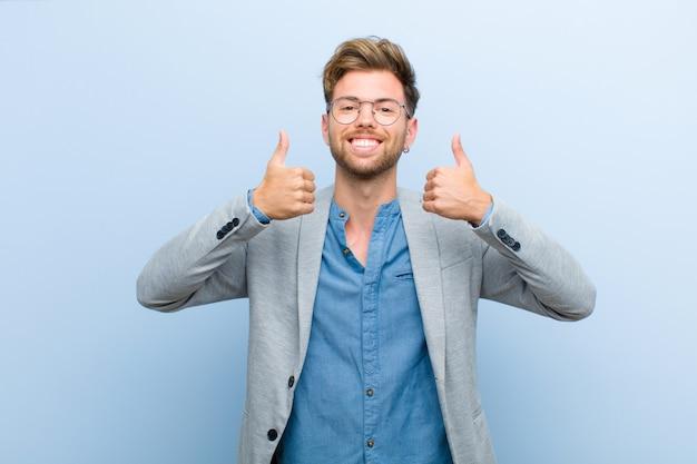 Молодой предприниматель, улыбаясь широко глядя счастливым, позитивным, уверенным и успешным, с обоими пальцами вверх