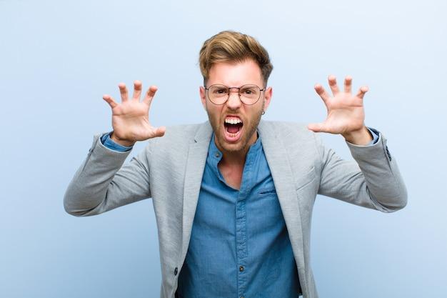 Молодой бизнесмен кричал в панике или гневе, шокирован, испуган или в ярости, с руками рядом с головой