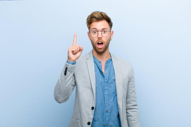 Молодой бизнесмен, чувствуя себя счастливым и возбужденным гением после реализации идеи, весело поднимая палец, эврика!