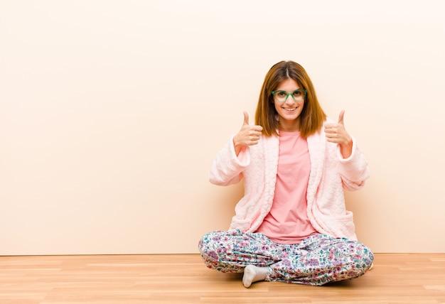 Молодая женщина в пижаме, сидя дома, широко улыбаясь, счастливые, позитивные, уверенные и успешные, с большими пальцами руки вверх