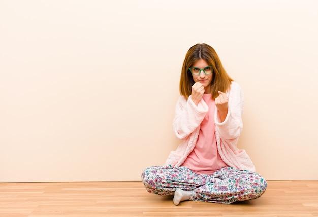自信を持って、怒って、強くて攻撃的な、ボクシングの位置で戦う準備ができて拳で家に座っているパジャマを着た若い女性