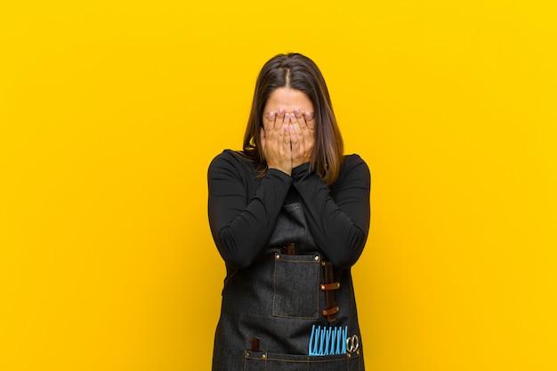 Женщина-парикмахер чувствует грусть, разочарование, нервозность и депрессию, закрывает лицо обеими руками, плачет