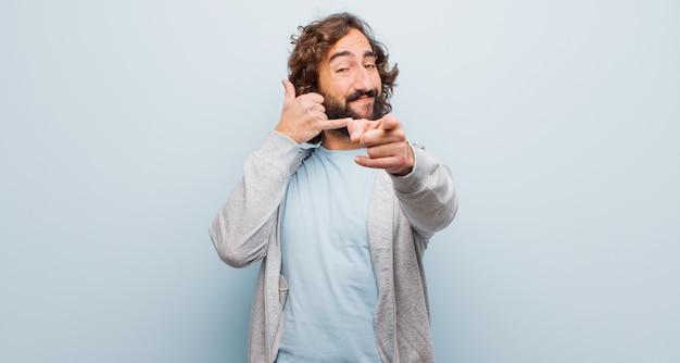 Молодой бородатый сумасшедший, весело улыбаясь и указывая, делая жест позже позвонив вам, разговаривая по телефону с плоской цветной стеной