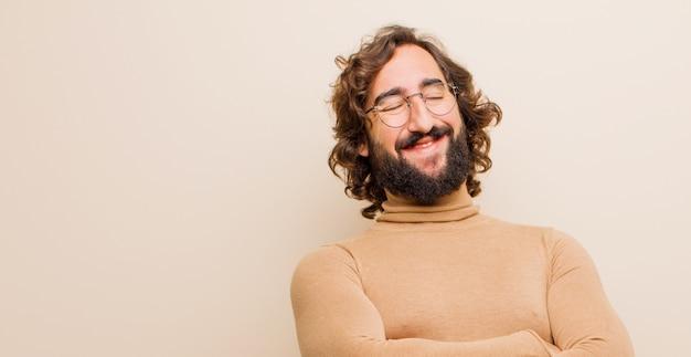 Молодой бородатый сумасшедший, счастливо смеющийся со скрещенными руками, в расслабленной, позитивной и довольной позе на плоской цветной стене