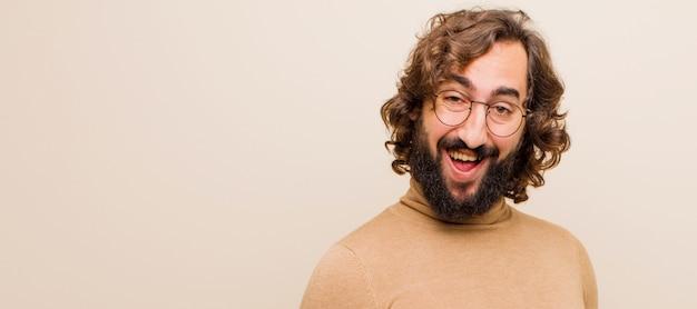 Молодой бородатый сумасшедший с широкой, дружелюбной, беззаботной улыбкой, выглядит позитивно, расслабленно и счастливо, пугающий на ровной цветной стене