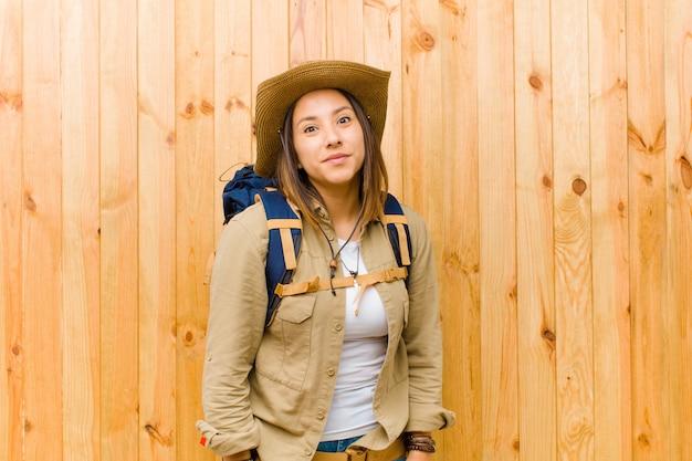 木製の壁を背景に若いラテンエクスプローラー女性