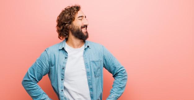 Молодой бородатый сумасшедший мужчина выглядит счастливым, веселым и уверенным, гордо улыбается и смотрит в бок обеими руками на бедра