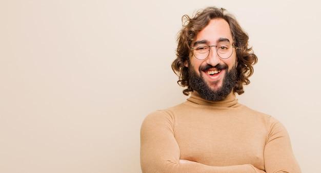Молодой бородатый сумасшедший, выглядящий как счастливый, гордый и довольный, улыбающийся со скрещенными руками