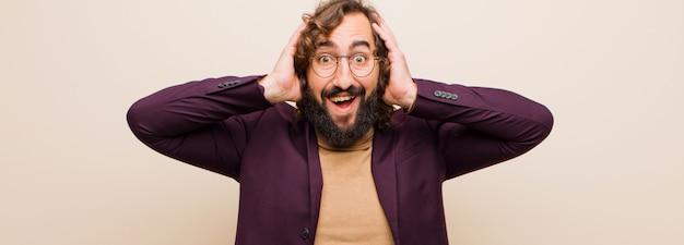 Молодой бородатый сумасшедший мужчина выглядит счастливым, беззаботным, дружелюбным и расслабленным, наслаждаясь жизнью и успехом, с позитивным настроем