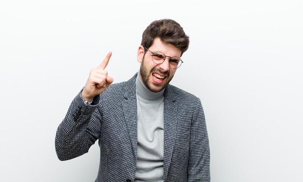 白い壁に対して猛烈な、狂った上司のように見える怒っている積極的な表現で指している若いマネージャー男