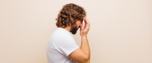 悲しい、イライラした絶望、泣き、サイドビューの手で目を覆っている若いひげを生やした狂気の男