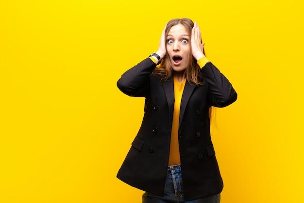 Молодая красивая деловая женщина смотрит неприятно шокирован, напуган или обеспокоен, широко открыт рот и закрывает оба уха руками на оранжевом фоне