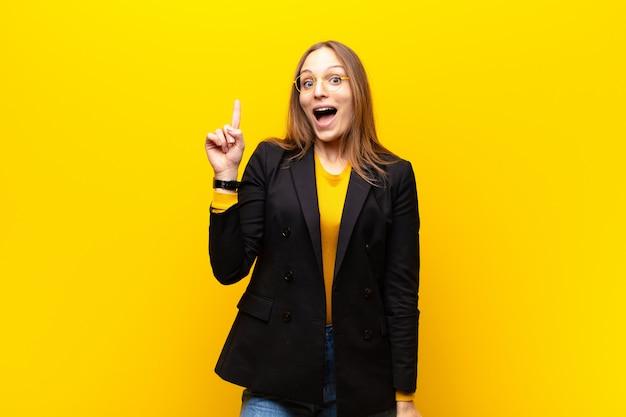 Молодая симпатичная деловая женщина, чувствуя себя счастливым и возбужденным гением после воплощения идеи, весело поднимая палец, эврика! на оранжевом фоне