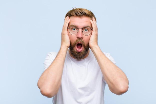 不愉快なショックを受けた、怖い、心配している若い金髪の成人男性、口を大きく開いて両手で耳を覆っている