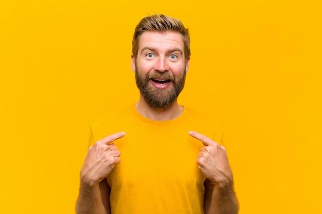 オレンジ色の壁に対して興奮して、驚いた表情で自己を指している幸せ、驚き、誇りに思って若いブロンドの男