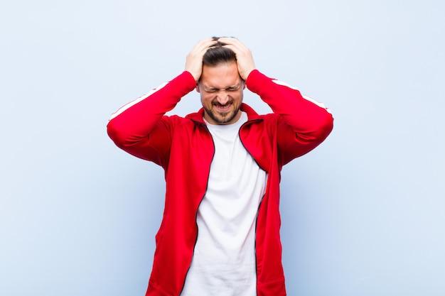 若いハンサムなスポーツの男性またはモニターのストレスやイライラ感、頭に手を上げて、疲れて、不幸な感じと片頭痛と平らな壁