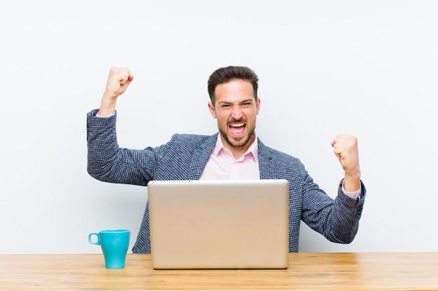Молодой красивый бизнесмен торжествующе кричит, выглядит как возбужденный, счастливый и удивленный победитель, празднуя