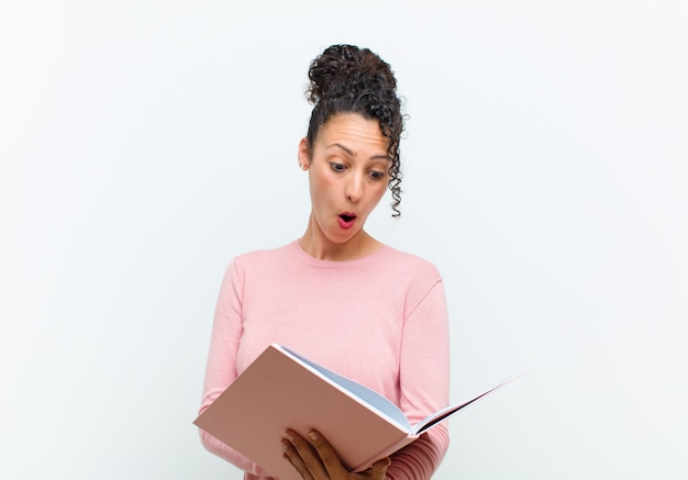 白い壁に本を持つ若いきれいな女性