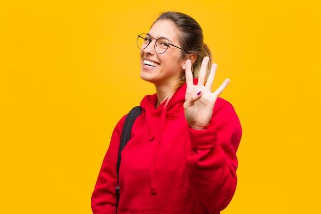Молодой симпатичный студент улыбается и смотрится дружелюбно, показывая номер четыре или четвертый рукой вперед, считая