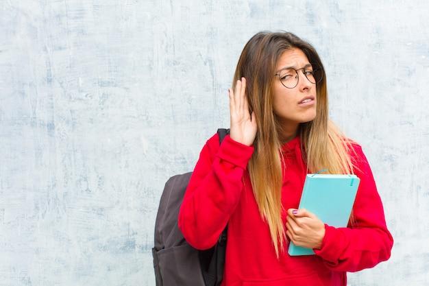 真面目で好奇心が強く、聞いて、秘密の会話やゴシップを聞き取ろうとして、盗聴している若い可愛い学生