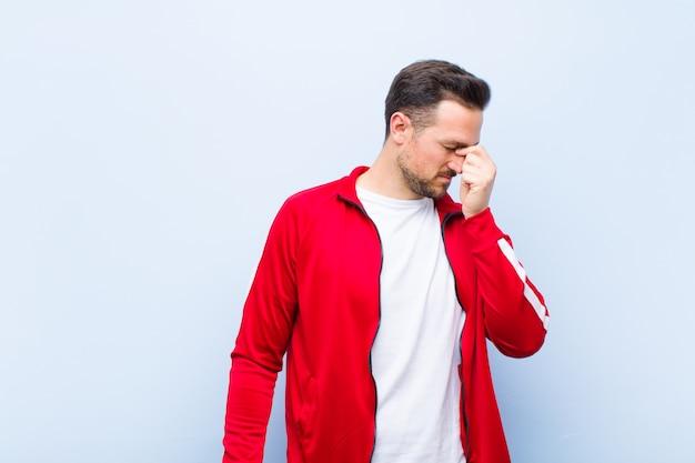 若いハンサムなスポーツ男またはモニター感じてストレス、不幸とイライラ、額に触れると平らな壁に激しい頭痛の片頭痛に苦しんでいます。