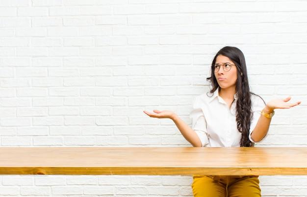 Молодая симпатичная латинская женщина выглядит озадаченной, растерянной и напряженной, размышляя о разных вариантах, чувствуя себя неуверенно, сидя перед столом