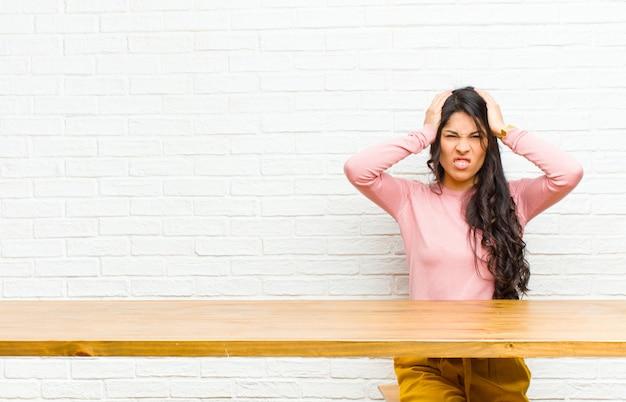 欲求不満とイライラ、病気と失敗にうんざりし、テーブルの前に座って退屈で退屈な仕事にうんざりしている若いかなりラテン女性