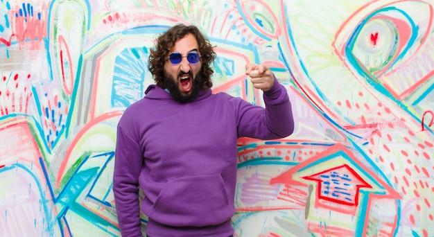 落書きの壁に対して猛烈な、狂った上司のように見える怒っている積極的な表現でカメラを指して若いひげを生やした狂気の男