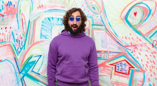 Молодой бородатый сумасшедший человек в ужасе и шоке, с широко раскрытым ртом от граффити стены