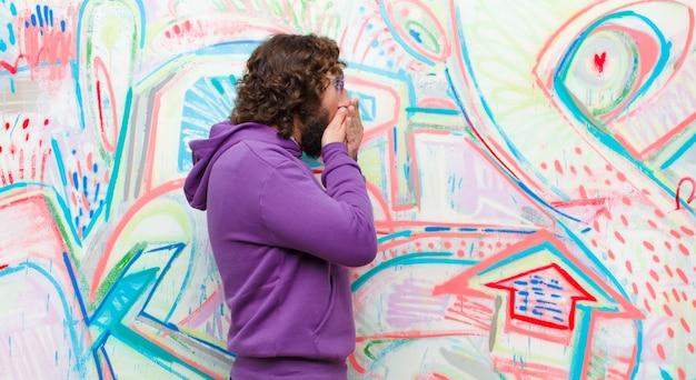 Молодой бородатый сумасшедший человек закрывает глаза руками с грустным, разочарованным видом отчаяния, плача, вид сбоку на стену граффити