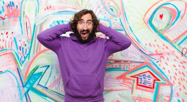 Молодой бородатый сумасшедший мужчина выглядит озадаченным, растерянным и напряженным, размышляя о разных вариантах, чувствуя себя неуверенно на фоне граффити
