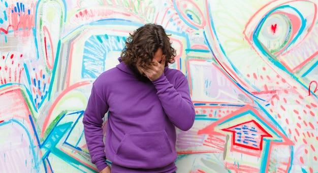 Молодой бородатый сумасшедший чувствуя грусть, разочарование, нервозность и депрессию, закрывая лицо обеими руками, плача против граффити стены