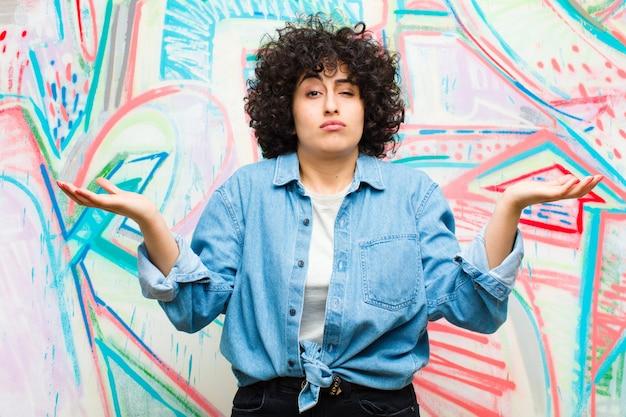 Молодая симпатичная афро женщина выглядит озадаченной, растерянной и напряженной, размышляя о разных вариантах, чувствуя себя неуверенно на фоне граффити
