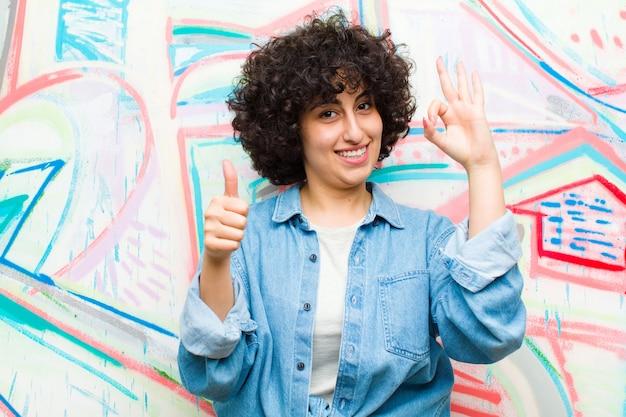 Молодая симпатичная афро женщина чувствует себя счастливой, изумленной, удовлетворенной и удивленной, показывает нормально и недурно жестами, улыбается на фоне граффити
