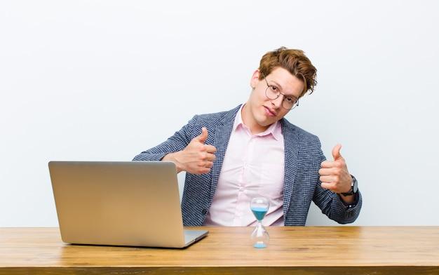 Молодой красный головной бизнесмен работая в его столе с часами. концепция времени