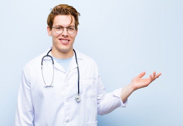 幸せ、驚き、陽気、前向きな姿勢で笑って、青い壁に対する解決策やアイデアを実現する若い赤ヘッド医師