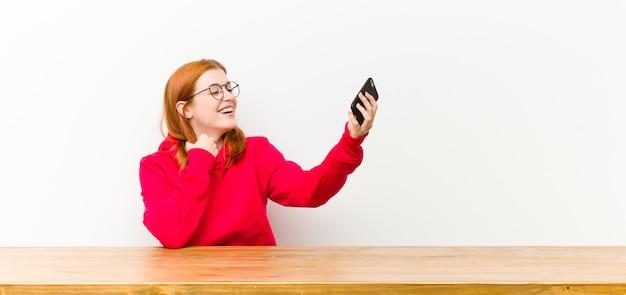 携帯電話で木製のテーブルの前に若い赤い頭のきれいな女性