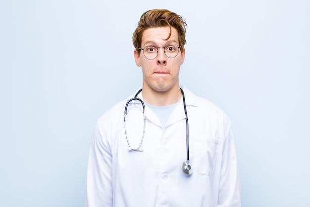 Молодой рыжий врач, чувствующий грусть и стресс, расстроенный из-за плохого удивления, с негативным, тревожным взглядом на синей стене